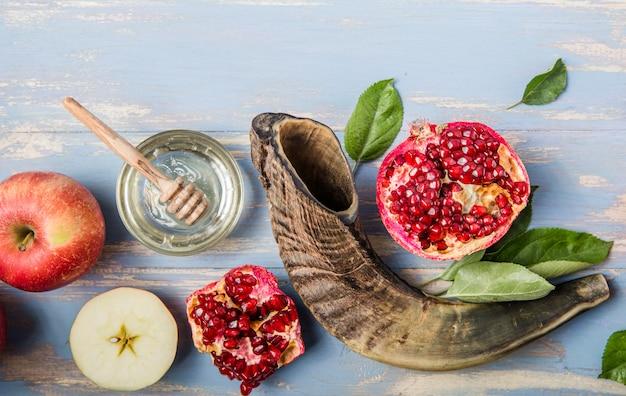 Rosh hashanah (hashana) - concetto di festa ebraica di capodanno. vaso di mele e mele fresche con melograno e shofar - corno su sfondo blu. copia spazio per il testo. vista dall'alto