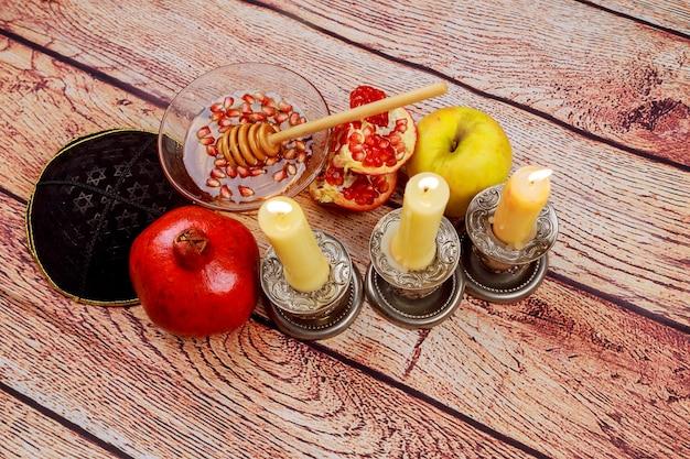 Rosh hashanah jewesh holiday concept libro di torah, miele, mela e melograno su un tavolo di legno. simboli di vacanza tradizionali.