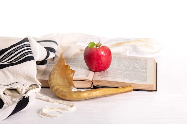 Rosh hashanah. yom kippur. tallit, shofar, torah, mela rossa su sfondo bianco. isolato