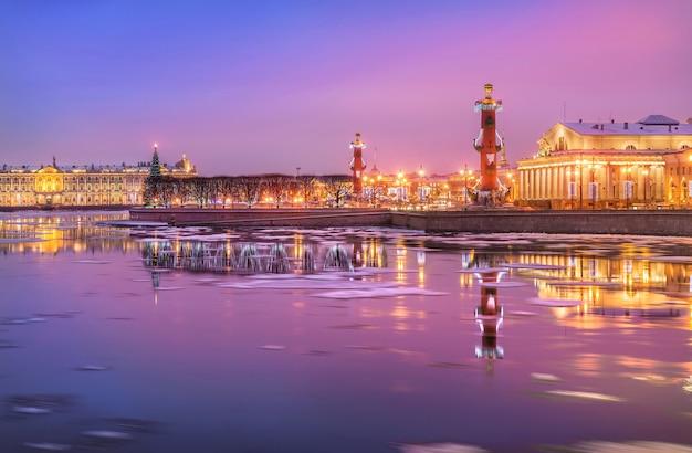 Colonne rostrale sulla strelka dell'isola vasilyevsky con un riflesso nel fiume neva a san pietroburgo in una mattina invernale rosa