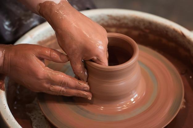 Ruota da vasaio rotante e ceramica su di essa vista dall'alto un ceramista fa una pentola su una ruota da vasaio