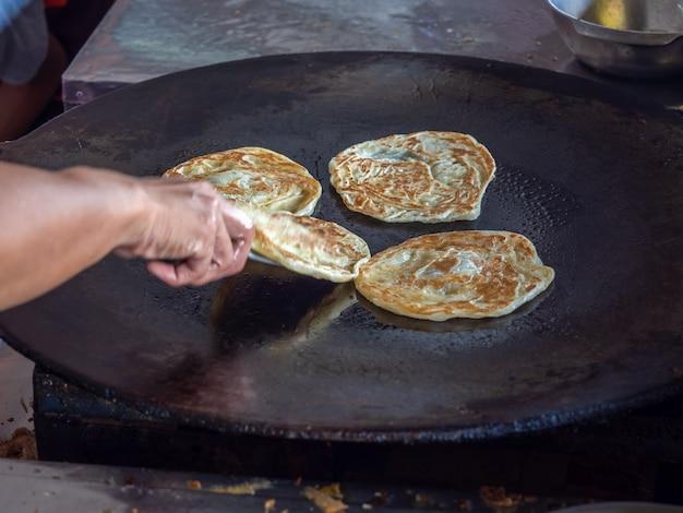 Roti making, roti e uovo fritto in padella. Foto Premium