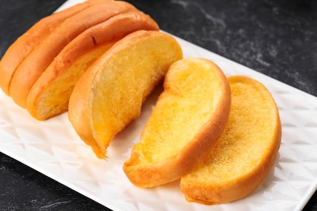 Roti sisir jadul, pane dolce e soffice fatto in casa con margarina e zucchero da spalmare. servito su piatto bianco, focus selezionato