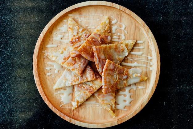 Roti con dessert al latte condensato servito su un piatto di legno