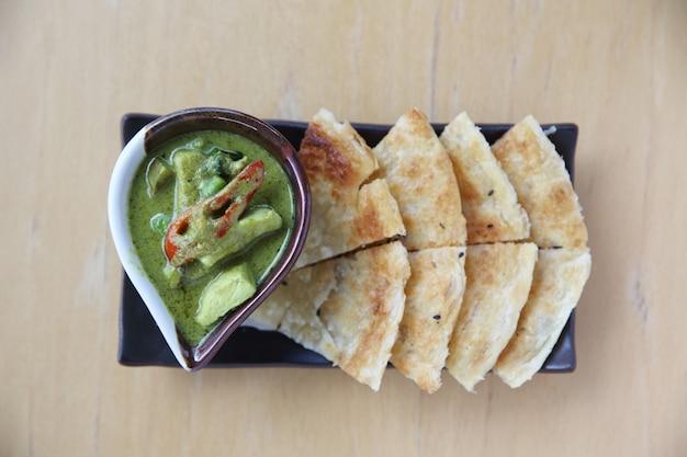 Roti al curry verde su fondo di legno