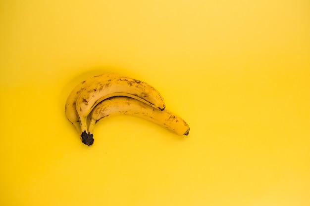 Banane marce su uno spazio giallo con spazio di copia. vista superiore di tre banane marce
