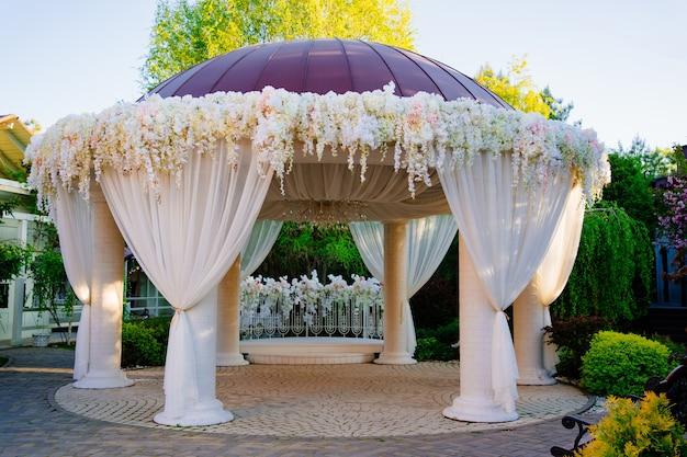 Rotonda per un matrimonio nel parco o in giardino. decorazione di gazebo e archi. lavoro di decoratore durante le vacanze e le attività all'aperto.