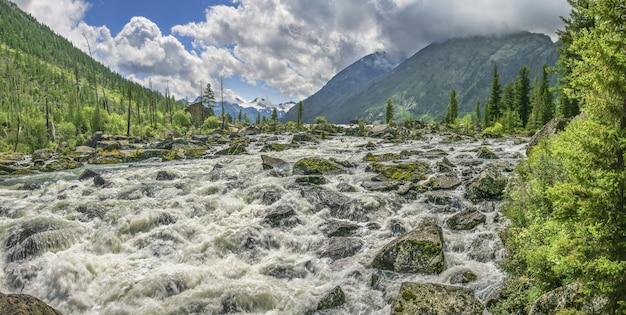 Ruvido fiume di montagna scorre tra le pietre, nuvoloso giorno d'estate