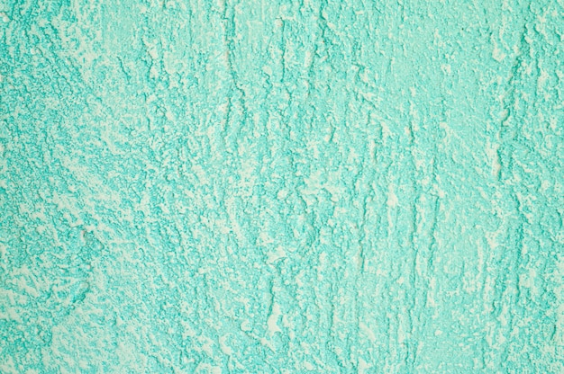 Struttura approssimativa di fondo verde chiaro decorativo astratto della parete del gesso.