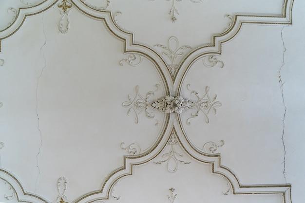 Modanatura in rilievo in stucco di argilla decorativa d'epoca rotonda antica con ornamenti floreali sul soffitto bianco in interni in stile classico astratto