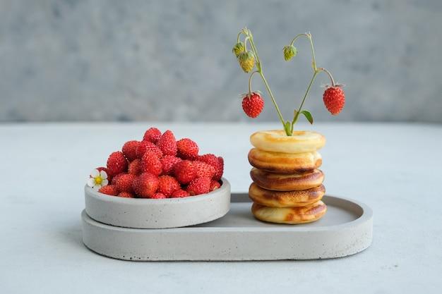 Ciambella al forno rotonda con fragole su uno sfondo di cemento. minimalismo. copia spazio