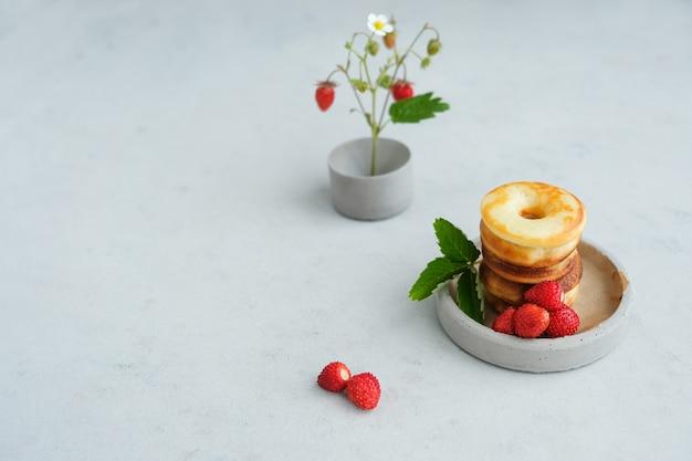 Ciambella al forno rotonda con fragole su fondo di cemento. minimalismo.
