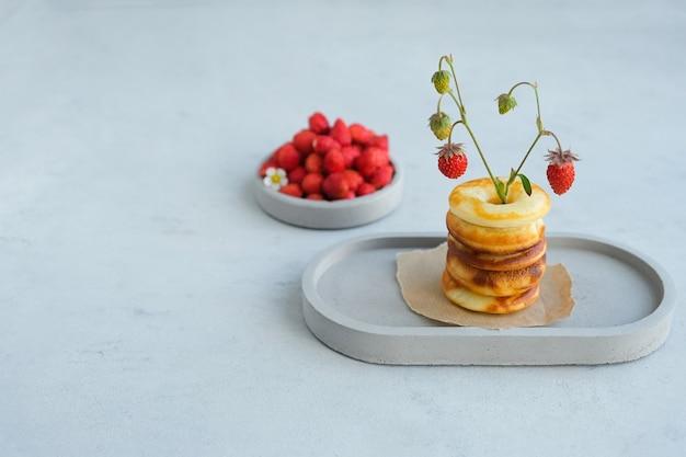Ciambella al forno rotonda con fragole su uno sfondo di cemento grigio. minimalismo.