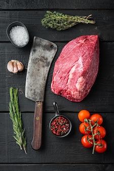 Round carne di manzo crudo impostato con il vecchio coltello da macellaio mannaia, sul tavolo in legno nero, vista dall'alto laici piatta