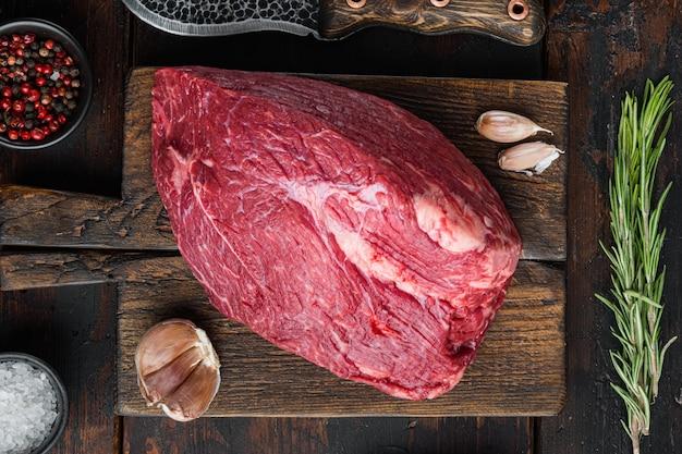 Insieme crudo di carne di manzo rotondo, sul tagliere di legno, sul vecchio tavolo in legno scuro, vista dall'alto laici piatta