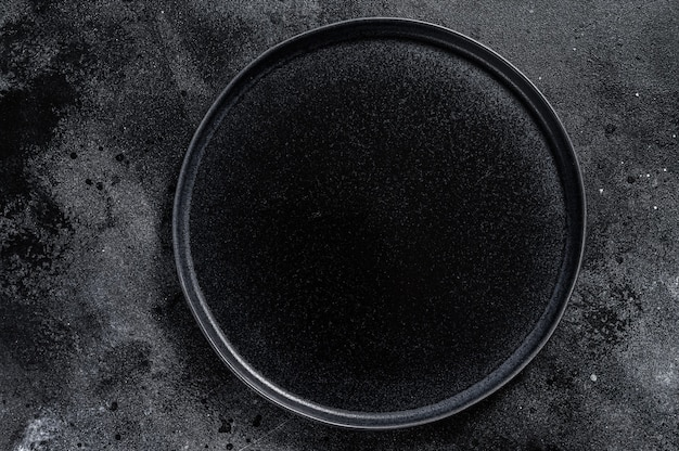 Piatto nero rotondo su superficie nera strutturata