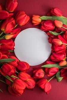 Scena di mock-up di biglietto di auguri in bianco rotondo e tulipani rossi su superficie rossa