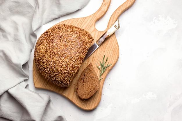 Pane tondo con semi di sesamo su uno spazio bianco. copia spazio