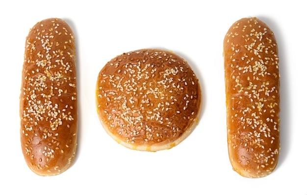 Panino rotondo e panino ovale al forno per hot dog, prodotti da forno cosparsi di semi di sesamo e isolato sul muro bianco, vista dall'alto