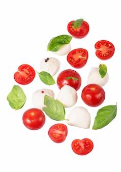 Formaggio camembert rotondo con pomodorini e basilico su un bianco