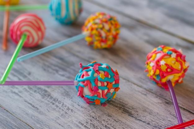 Caramelle rotonde su bastoncini. dolci su superficie di legno grigia. gustosa sorpresa per i bambini. cake pop con ripieno.