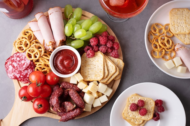 Un tagliere rotondo di salumi con salsiccia, formaggio, cracker e frutta, piatti con antipasto, primo piano.