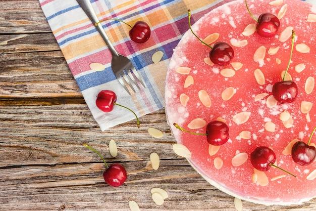 Cheesecake rotonda con ciliegie su superficie in legno vista dall'alto