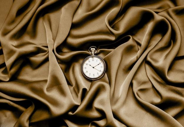 Orologio rotondo su uno sfondo di tessuto. salpare champagne