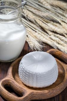 Ricotta rotonda in una ciotola con latte su un tavolo di legno.