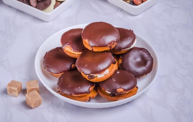 Torte rotonde alla crema con crema e cioccolato su un piatto bianco