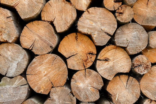 Legna da ardere rotonda accatastata a catasta di legna. struttura e fondo di legno.