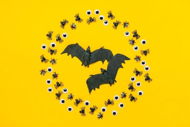Cornice rotonda di ragni neri e mosche, occhi finti e pipistrello all'interno. vista dall'alto piatto lay happy halloween concetto creativo holiday card.