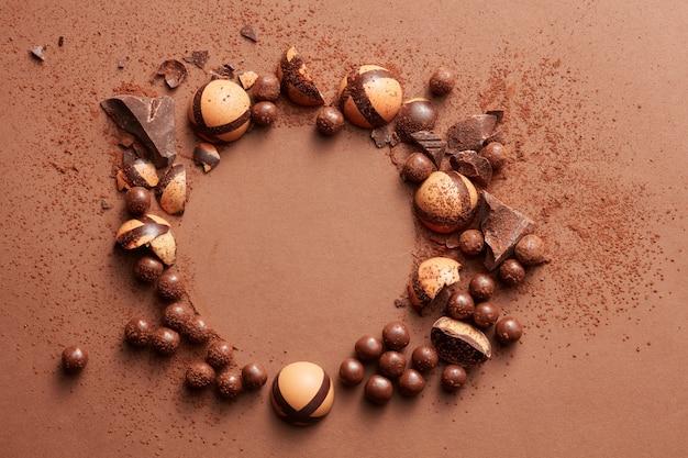 Cornice rotonda di cioccolatini su uno sfondo marrone