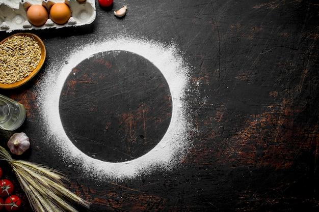 Cornice rotonda fatta di farina con spighette, grano e uova sul tavolo rustico scuro.