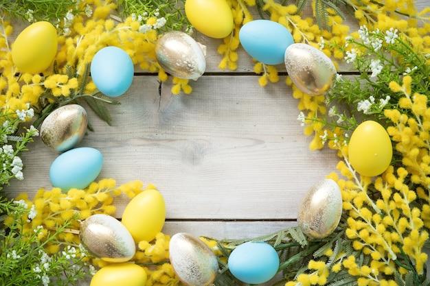 Cornice rotonda fatta di rami di mimosa e uova di pasqua su assi di legno