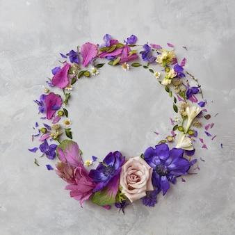 Cornice rotonda di fiori primaverili colorati su sfondo grigio