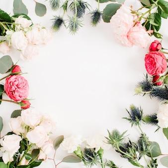 Corona rotonda con cornice fatta di fiori di rosa rossi e beige, fiori di eringium, rami di eucalipto e foglie isolati su sfondo bianco. disposizione piatta, vista dall'alto