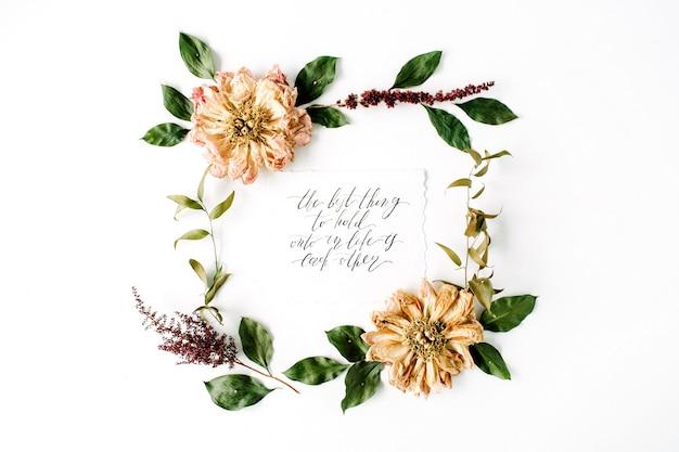 Modello di ghirlanda di cornice rotonda con citazione di ispirazione scritta in stile calligrafico, fiori di peonie essiccate beige, rami e foglie isolati su bianco