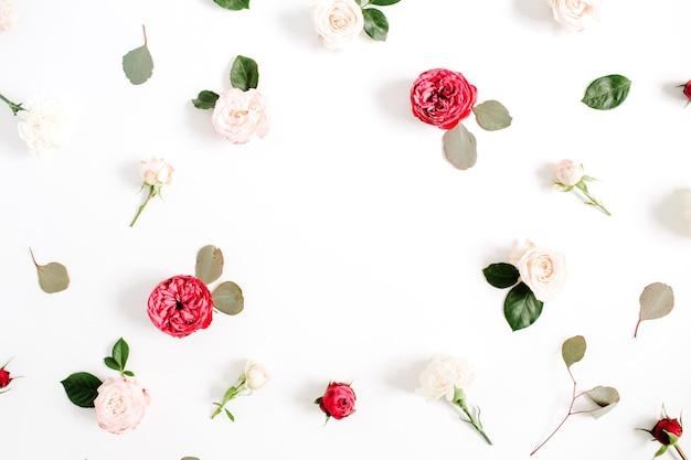 Modello di corona cornice rotonda con boccioli di fiori di rosa rossi e beige, rami e foglie isolati su priorità bassa bianca. disposizione piatta, vista dall'alto
