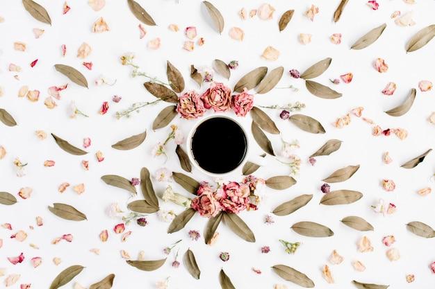 Modello di ghirlanda cornice rotonda con rose, tazza di caffè, boccioli di fiori rosa, rami e foglie secche su superficie bianca