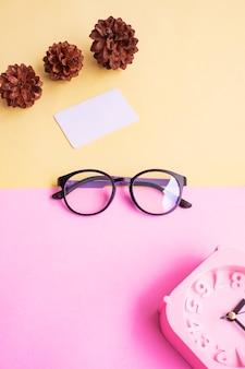 Occhiali rotondi nella foto in stile estivo minimale su sfondo rosa pastello e giallo. sveglia, fiori di pino, biglietti da visita