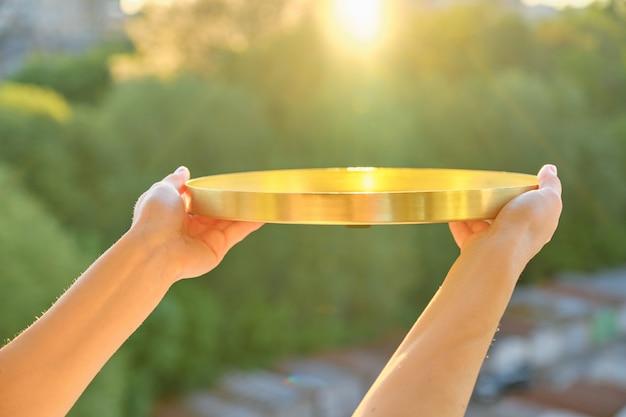 Vassoio rotondo d'ottone dorato del metallo in mani della donna, tramonto del fondo