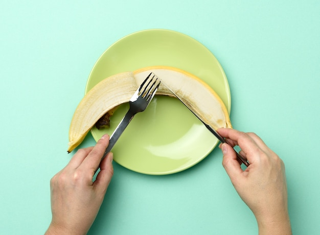 Piatto rotondo in ceramica verde con una banana intera, due mani tengono un coltello e una forchetta