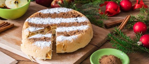 Torta di mele alla cannella fatta in casa rotonda su un tavolo di legno con decorazioni natalizie intorno