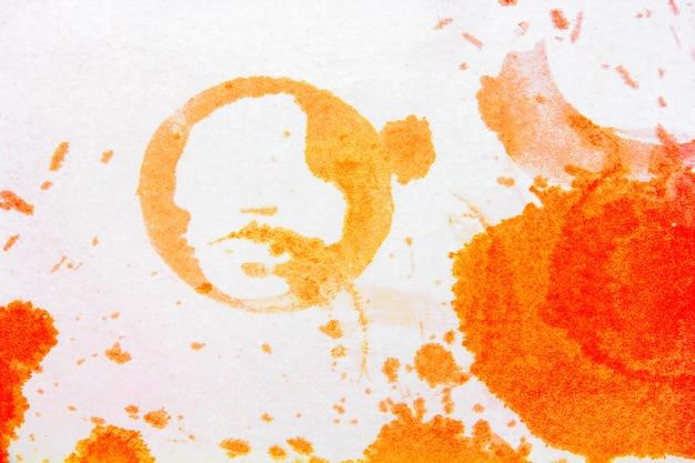 L'impronta rotonda del bicchiere di macchie arancioni luminose dal succo versato su una superficie bianca