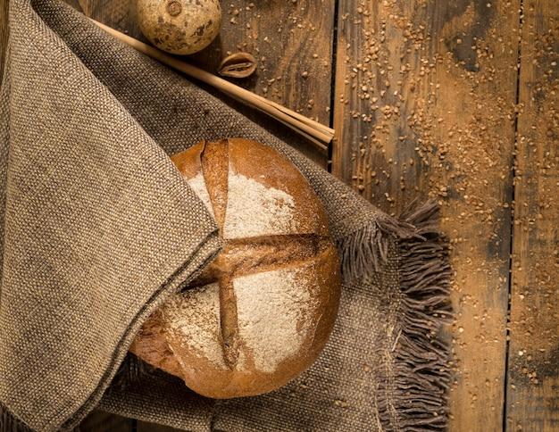 Pagnotta rotonda su un tovagliolo di stoffa e assi di legno con briciole