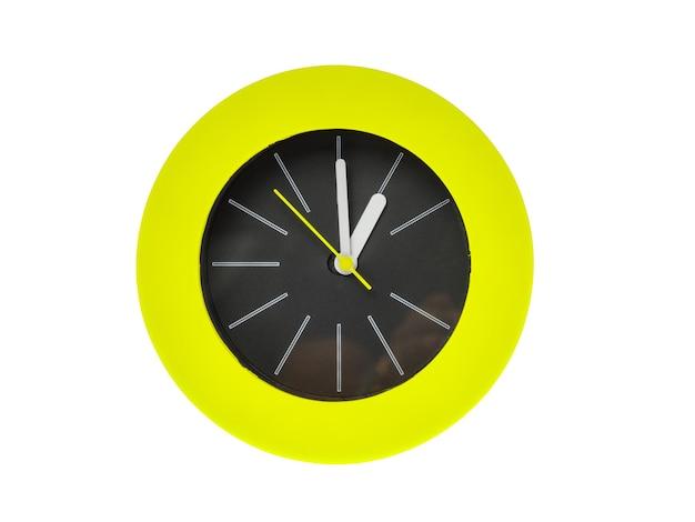 Orologio moderno rotondo con striscia bianca, sottili lancette gialle che puntano al centro possiedono l'ora, l'una di sera o l'una del mattino. la parte centrale dell'orologio è nera circondata da una fiamma circolare verde. isolato su bianco.