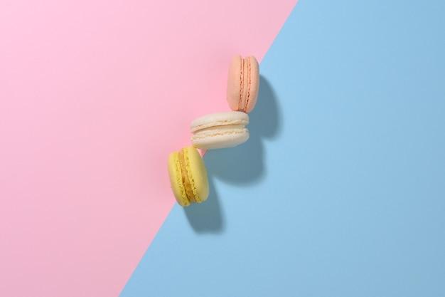 Macarons rotondi multicolori su una superficie rosa-blu con un'ombra. dessert gourmet di farina di mandorle, vista dall'alto