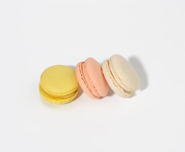 Macarons multicolori rotondi su una superficie bianca con un'ombra. dessert gourmet di farina di mandorle, vista dall'alto