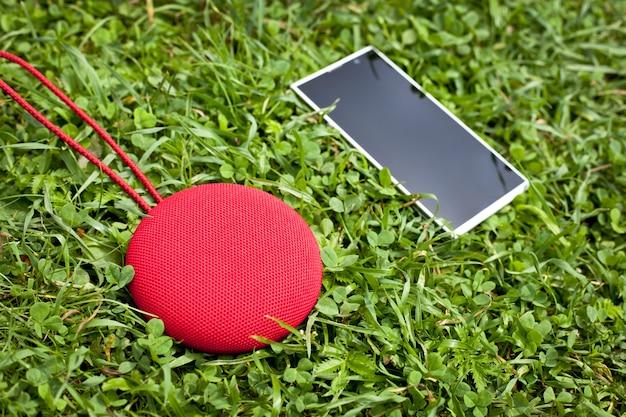 Altoparlante bluetooth di musica rotonda con smartphone sdraiato sull'erba.